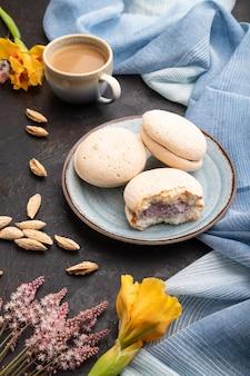 Ciasta bezy z filiżanką kawy na czarnej betonowej powierzchni i niebieskiej lnianej tkaninie