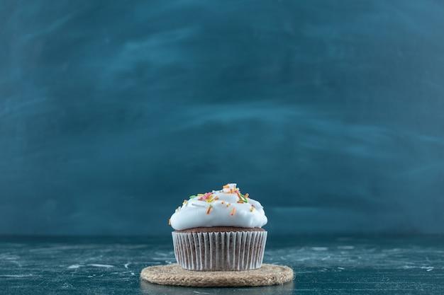 Ciasta brownie z kremem na podstawce, na niebieskim tle. zdjęcie wysokiej jakości