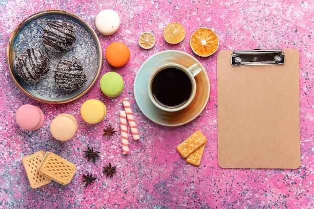 Ciasta czekoladowe z widokiem z góry z francuskimi makaronikami na jasnoróżowym tle