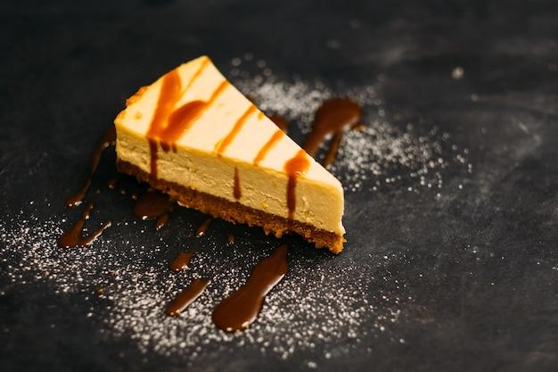 Ciasta i deser. zbliżenie nowojorski sernik z syropem i cukrem pudrem.