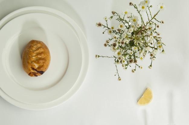 Ciasta i kwiaty rumianku na białej powierzchni z cieniem z kieliszków do wina