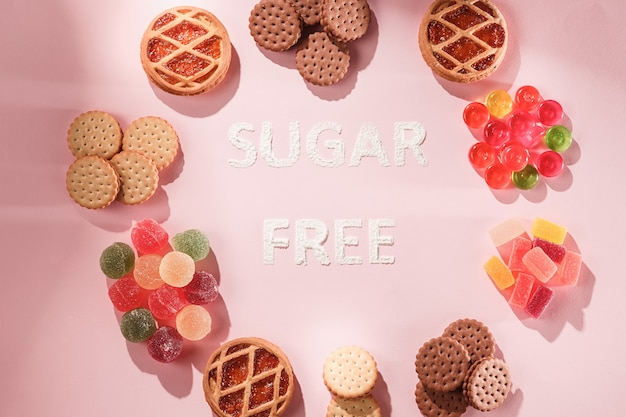 Ciasta i marmolady bez cukru. dietetyczne jedzenie. widok z góry na tle różowego stołu. zdrowa koncepcja.