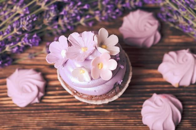 Ciasta lawendowe - babeczka i beza liliowa na drewnianym stole