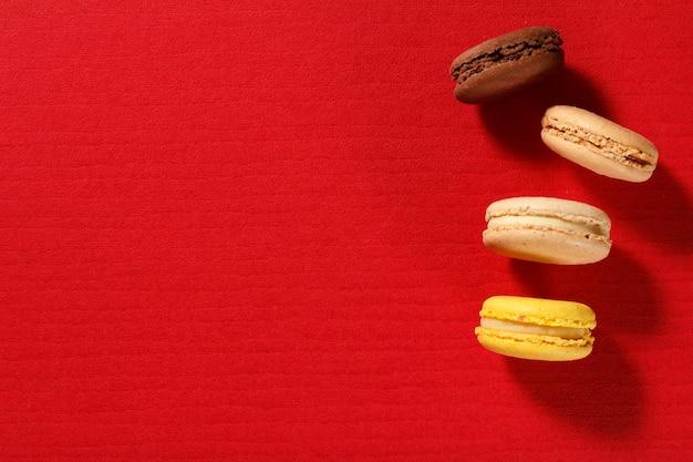 Ciasta macarons w innym kolorze na czerwonej powierzchni z teksturą. widok z góry