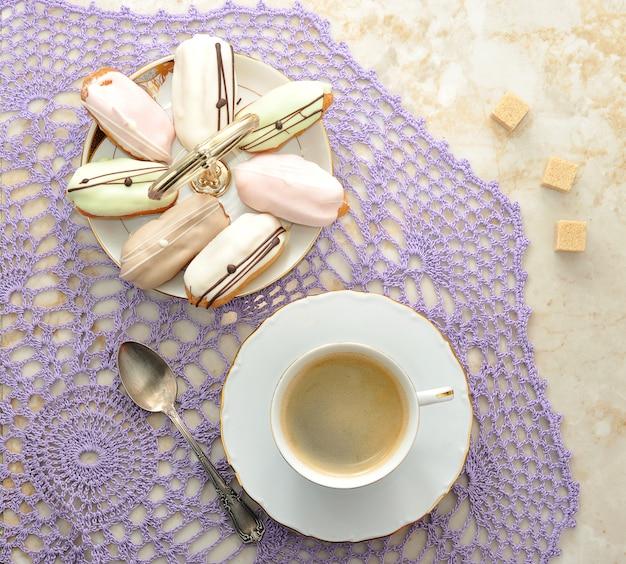 Ciasta na talerzu i kawa w kubku z łyżeczką i cukrem