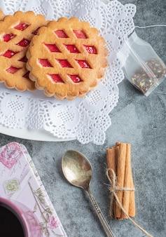 Ciasta owocowe i laski cynamonu na marmurze.