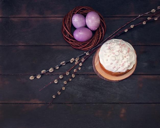 Ciasta wielkanocne na, ozdobione piankami i malowanymi pisankami w wiklinowym gnieździe, widok z góry