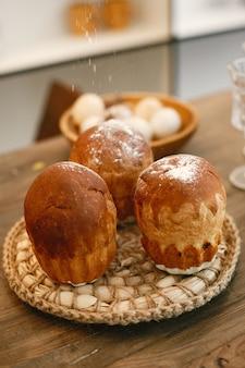 Ciasta wielkanocne na stole. pisanki na drewnianym talerzu. przygotowanie do wielkanocy.