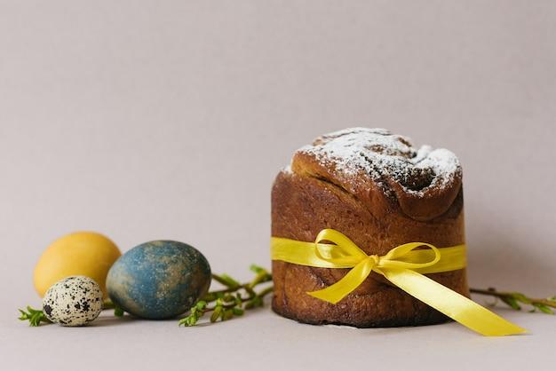 Ciasta wielkanocne (prawosławny tort wielkanocny), jajka i gałęzie forsycji. scena świąt wielkanocnych. świąteczna kompozycja na stole