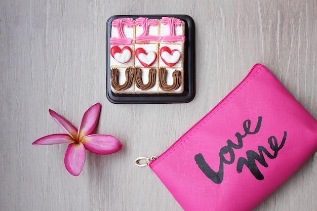 """Ciasta ze słowem """"kocham cię"""", kwiat frangipani i kosmetyczka z napisem kochaj mnie."""