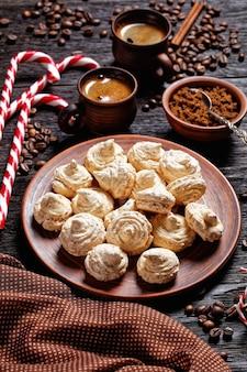 Ciasteczka bezowe podawane na talerzu z bożonarodzeniową trzciną cukrową, filiżankami kawy, ziarnami kawy, brązowym cukrem i laskami cynamonu na ciemnym drewnianym tle, widok z góry, zbliżenie