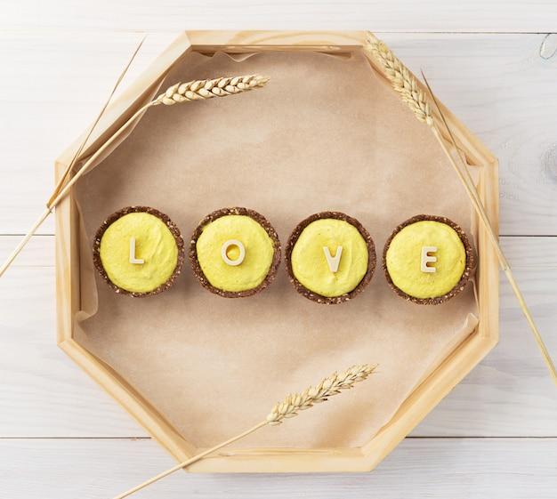 """Ciasteczka cytrynowe z nerkowcami z napisem """"love"""" w białej czekoladzie na drewnianej tacy."""