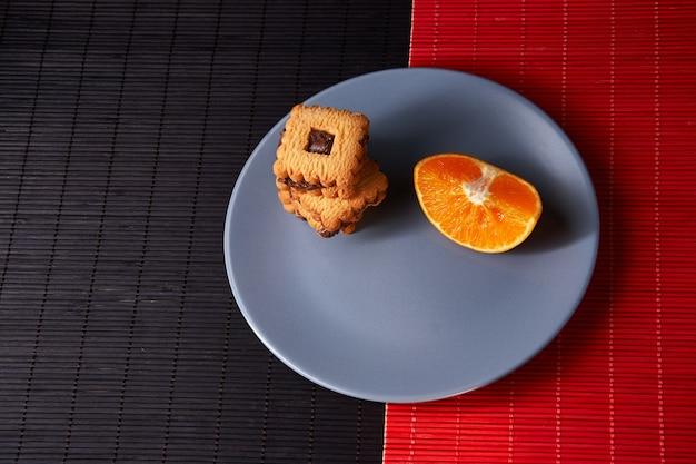 Ciasteczka czekoladowe i kawałek pomarańczy na talerzu i na tle czerwonym i czarnym