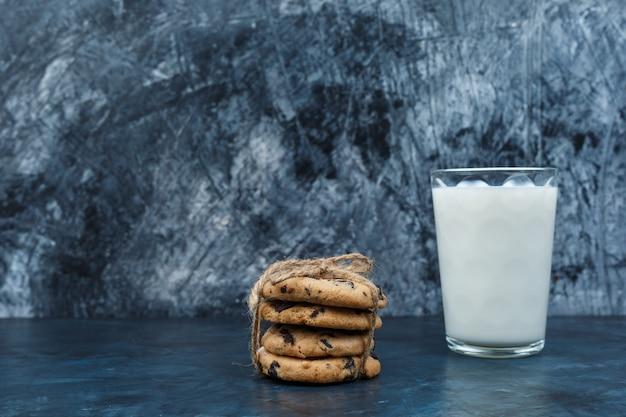 Ciasteczka czekoladowe i mleko na ciemnym niebieskim tle marmuru. zbliżenie.