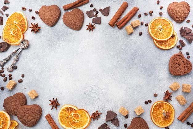 Ciasteczka czekoladowe serca, pomarańcze cynamonowe i pikantne przyprawy na szarym stole, widok z góry, miejsce.