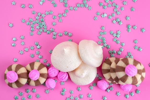Ciasteczka czekoladowe z widokiem z góry i bezy na różowym biurku, cukierkowy kolor ciasteczka