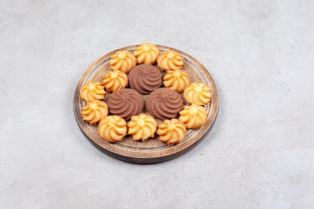 Ciasteczka dekoracyjnie ułożone na desce na marmurowym tle. wysokiej jakości zdjęcie