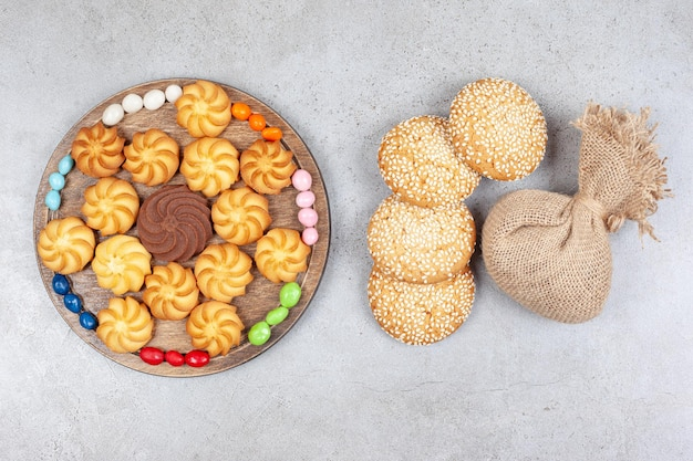 Ciasteczka i cukierki na desce obok ciasteczek i worek na tle marmuru. wysokiej jakości zdjęcie