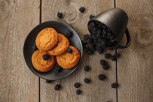 Ciasteczka i jeżyny na drewnianym tle