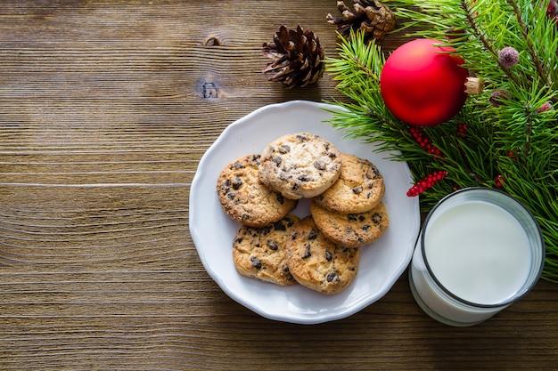 Ciasteczka i mleko dla śnięty mikołaj na drewnianym tle