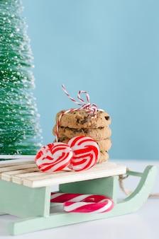 Ciasteczka i słodycze bożego narodzenia na drewnianych saniach z drzewem
