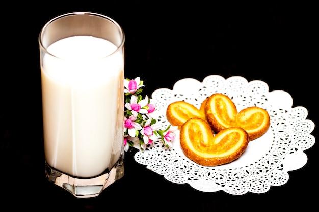 Ciasteczka i szklanka mleka - zdrowe śniadanie. drewniany stół. zbliżenie.