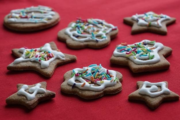 Ciasteczka imbirowe ze świątecznym wystrojem na czerwonym tle