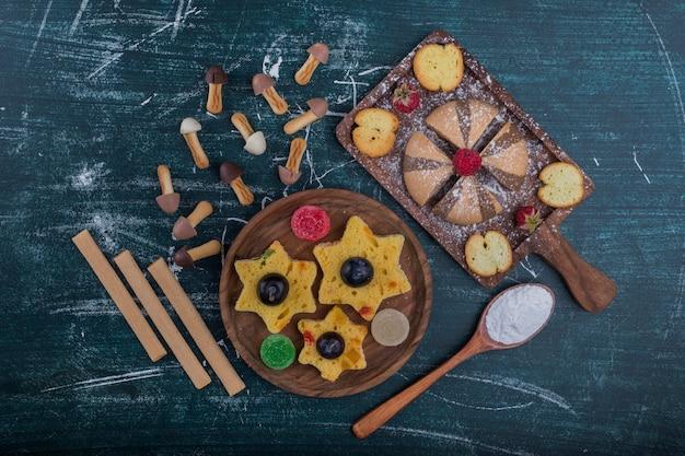 Ciasteczka kakaowe i waniliowe na drewnianej desce z ciasteczkami w kształcie gwiazdy
