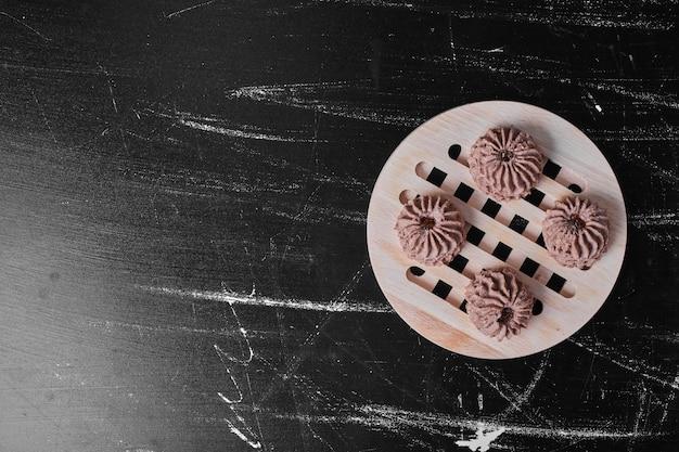 Ciasteczka kakaowe na drewnianym talerzu.