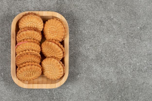 Ciasteczka kanapkowe wypełnione śmietaną na drewnianym talerzu