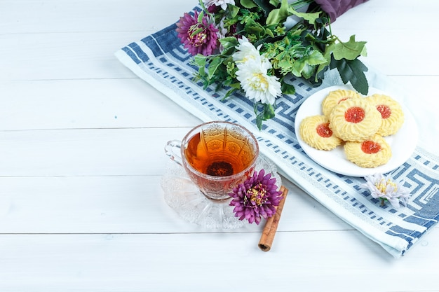 Ciasteczka, kwiaty na podkładce z cynamonem, filiżanka herbaty