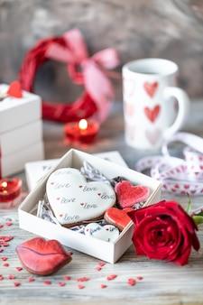 Ciasteczka lub pierniki w pudełku z czerwoną wstążką na drewnianym stole. walentynki.