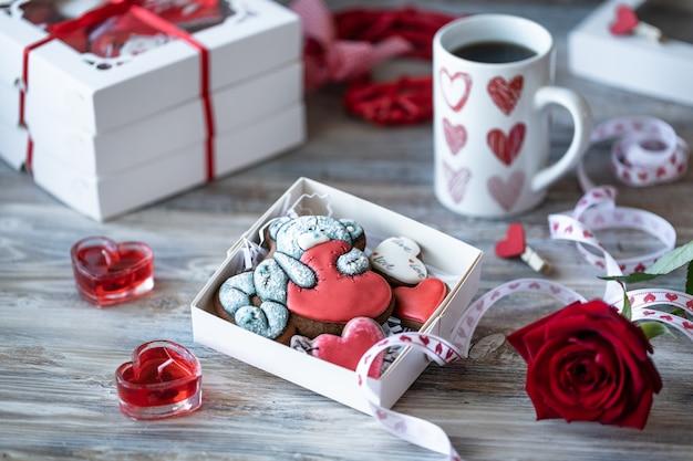 Ciasteczka lub pierniki w pudełku z czerwoną wstążką na drewnianym stole.