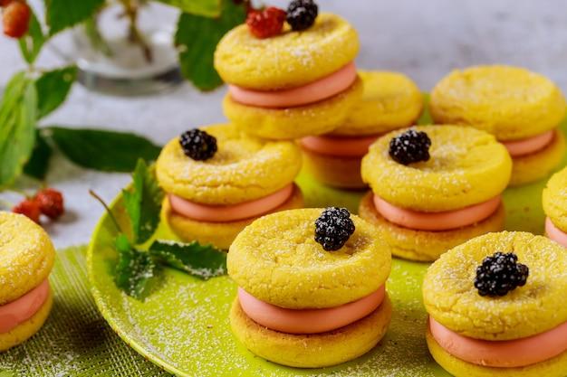 Ciasteczka lub słodkie kanapki z różową śmietaną i jagodami.