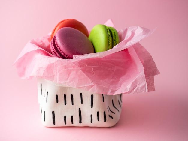 Ciasteczka makaronikowe leżą w koszu na różowym tle. widok z boku, pyszny i słodki deser