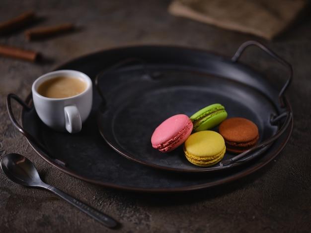 Ciasteczka makaronikowe na tacy vintage i filiżankę espresso