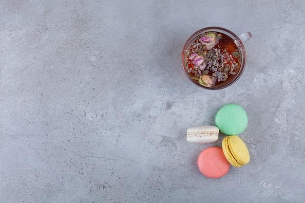 Ciasteczka makaronowe w różnych kolorach z szklaną filiżanką herbaty ziołowej.