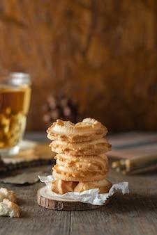 Ciasteczka maślane ułożone i szklanka herbaty na tle stołu z drewna, pionowe zdjęcie.