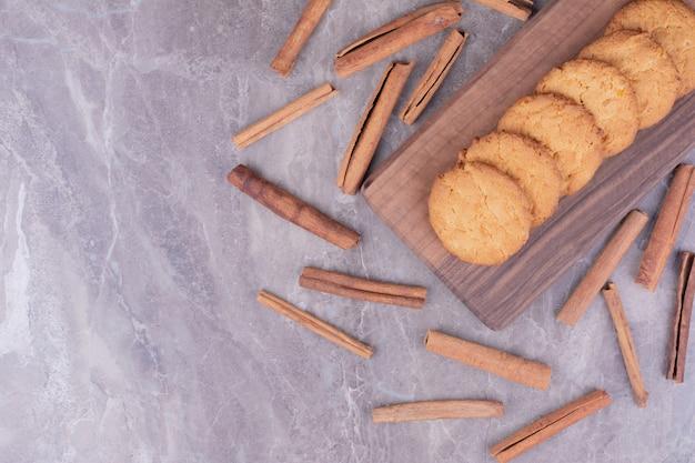 Ciasteczka maślane z laskami cynamonu na drewnianym talerzu