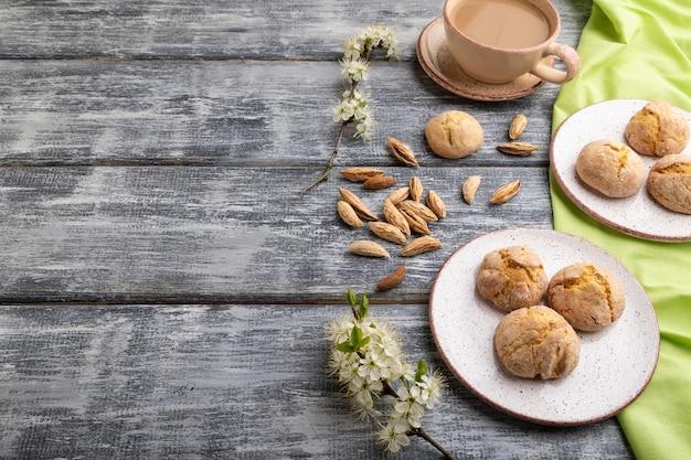 Ciasteczka migdałowe i filiżanka kawy na szarym drewnianym stole i zielonej lnianej tkaninie. widok z boku, miejsce na kopię.