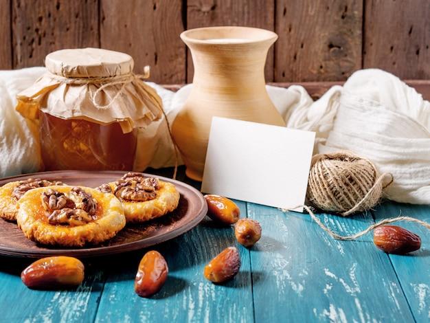 Ciasteczka, miód, daty, dzbanek na mleko i kartę na turkusowym drewnie