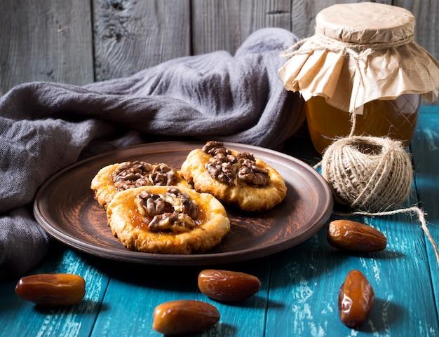 Ciasteczka, miód i daty na turkusowym drewnie