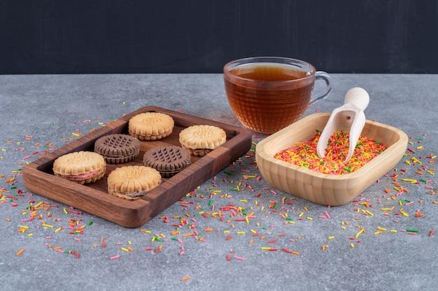 Ciasteczka, miska cukierków posypana i filiżanka herbaty