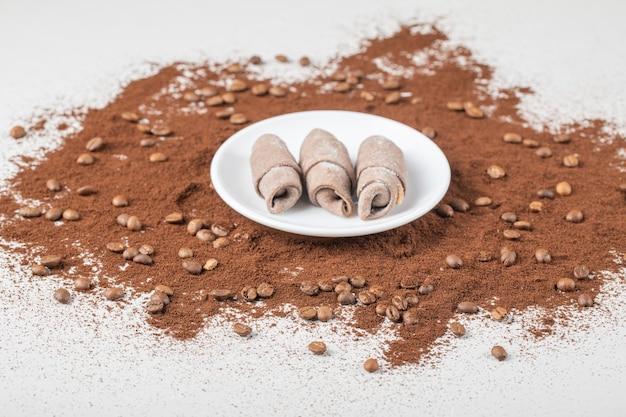 Ciasteczka mutaki w białym talerzu na zmiksowanej kawie mielonej.