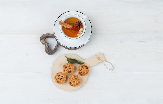Ciasteczka na drewnianej desce z filiżanką herbaty