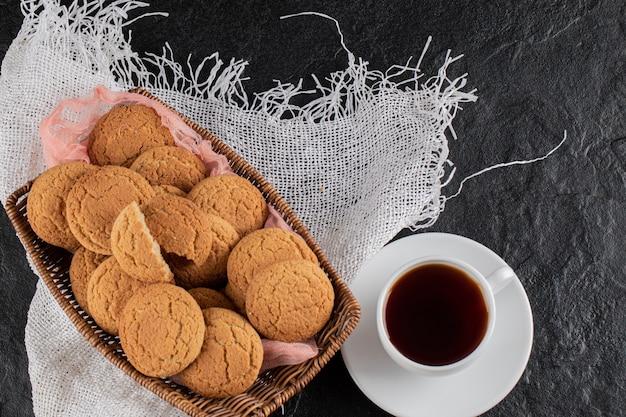 Ciasteczka na drewnianym talerzu podawane z filiżanką herbaty.