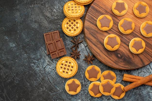 Ciasteczka na drewnianym talerzu z cynamonami i batonami czekoladowymi na szarym tle