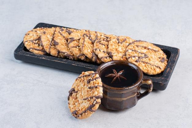 Ciasteczka na małej tacy obok filiżanki herbaty na marmurowym stole.