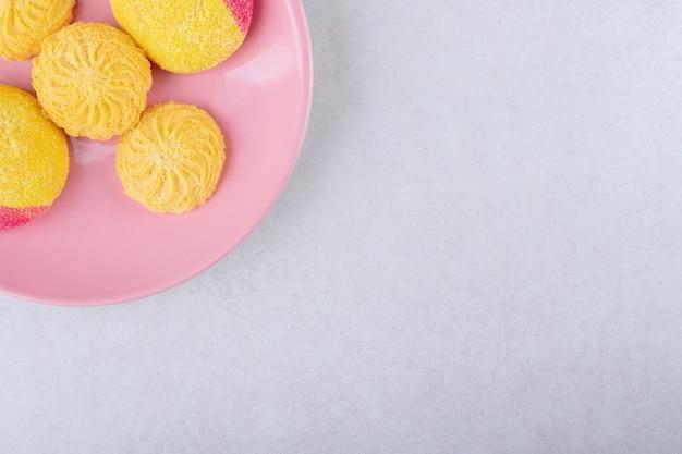 Ciasteczka na różowym talerzu na marmurowym stole.