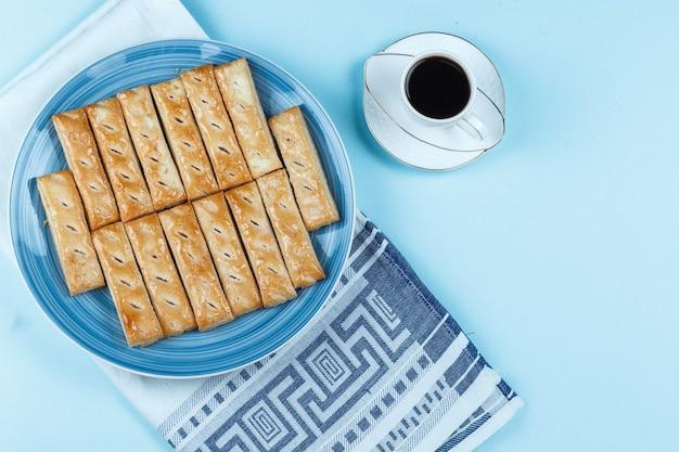 Ciasteczka na talerzu i filiżanka kawy na niebieskim tle
